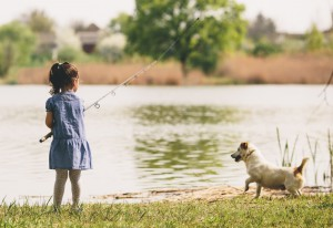girl fishing with a dog
